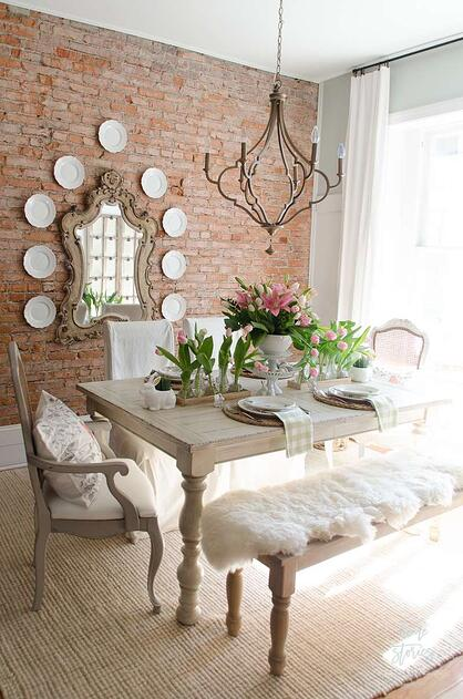 french farmhouse dining room with exposed brick wall, chandelier and light wood dining table