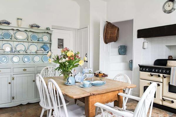 white and blue dining room kitchen area with traditional white arger stove and patterned plates