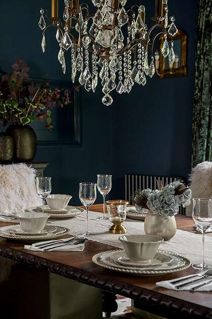 elegant dark royal blue dining room with chandelier and set table