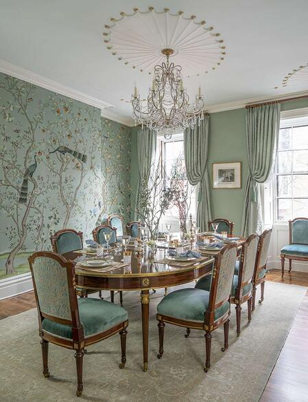 sea foam green dining room with patterned coloured wallpaper and matching dining chairs with chandelier overhead