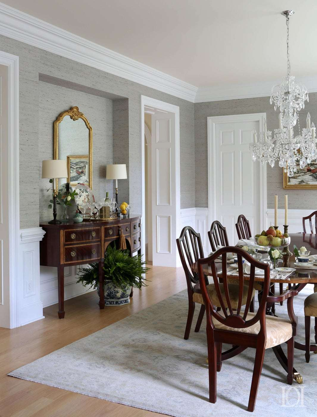 classy dining room with light grey walls, dark wooden dining table and chandelier