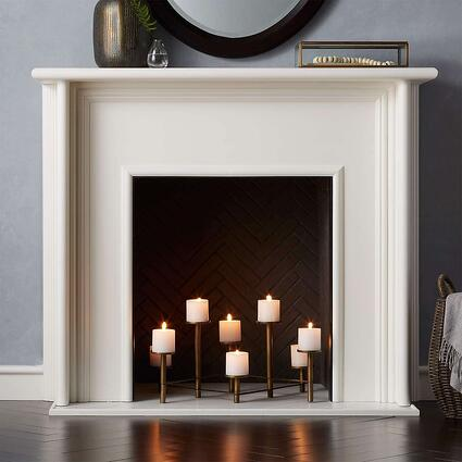 white false fireplace with candles clustered in the middle