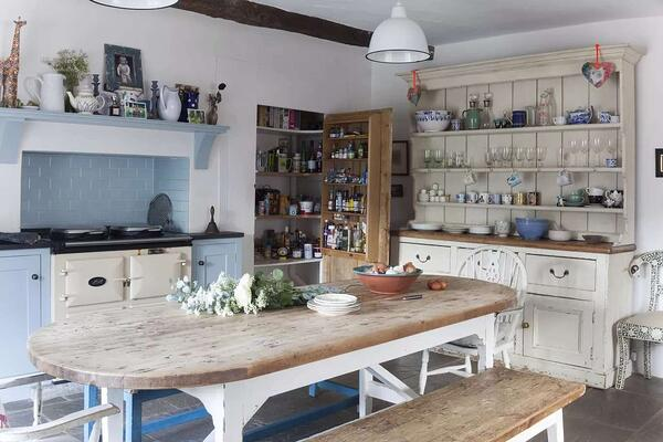 rustic wood dining table in cream and blue themed kitchen and dining area