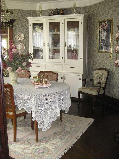white and pink dining room with lacy table cloth, dark wood dining table and flower patterned wallpaper