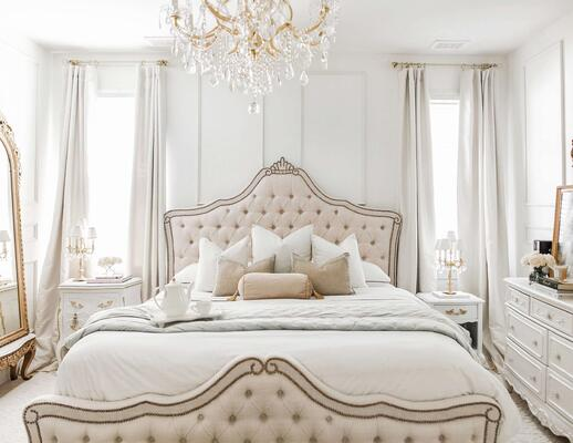 white french-inspired bedroom with upholstered headboard and footboard and gold chandelier