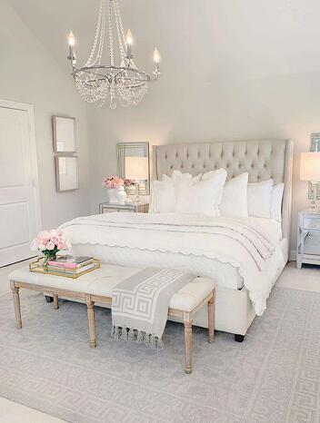 white bedroom with high headboard and chandelier