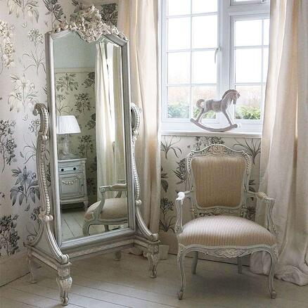 cream bedroom with matching chair and ornate full length mirror