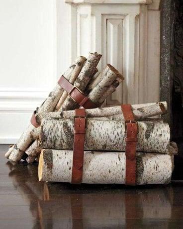 stacks of firewood logs held in bundles using brown leather behs
