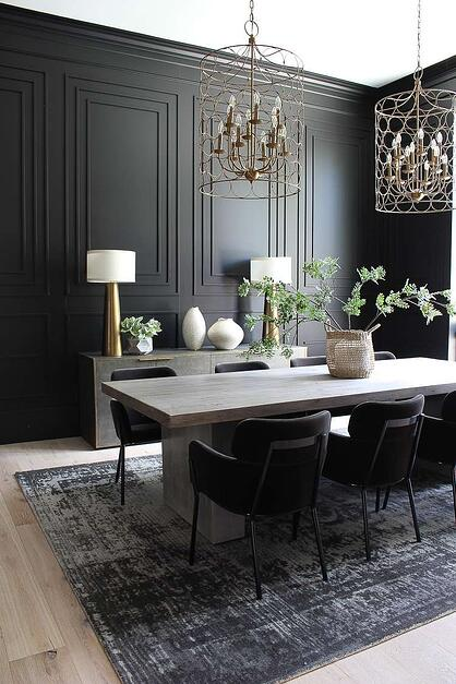 sleek dining room with black panneled walls and art deco inspired gold hanging light shades and side board.