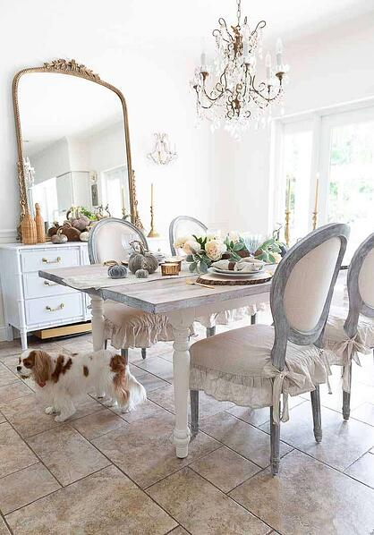 hite french themed dining room with distressed wood dining table in the centre and antique mirror on the wall