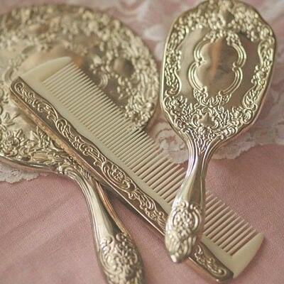 gold ornate vanity set of hand mirror, comb and brush on pink surface